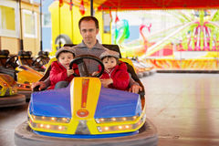 Father and his two sons, having a ride in the bumper car Royalty Free Stock Images