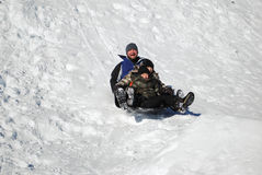Father and his two sons sledding Stock Photo