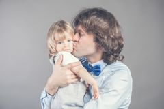 Father with his young baby cuddling and kissing her on cheek. Happy parenthood, love. Bunch of kisses from daddy makes stock photos