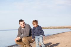 Father with his young son at the beach. Smiling father with his young son at the beach crouching down on the sand with a smile as the boy stands alongside him royalty free stock images