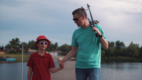 Father and his young son fishing in the evening. At a tranquil lake walking along the jetty hand in hand carrying their rods and smiling happily Stock Images