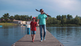 Father and his young son fishing in the evening. At a tranquil lake walking along the jetty hand in hand carrying their rods and smiling happily Stock Photography