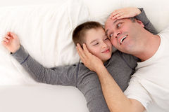 Father and his young son playing in bed Royalty Free Stock Photo