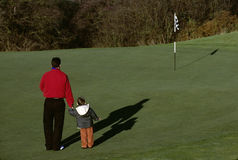 Father and son playing golf Stock Images