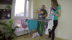 Father hold newborn baby child and mother pick laundry. 4K stock footage