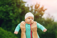 Father holding baby at arm`s length royalty free stock image