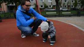 Father holding baby by the back, helping him to stand stock footage