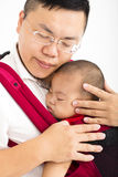 Father holding a baby. In a baby carrier royalty free stock image