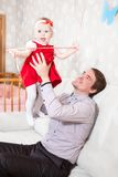 Father holding baby daughter in hands while sitting on sofa Royalty Free Stock Photo