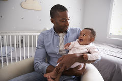 Father Holding Baby Daughter In Nursery Stock Photo
