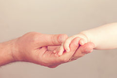 Father holding baby hand Stock Photo