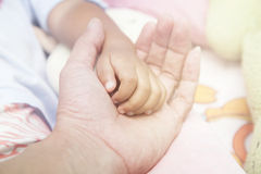 Father holding baby hand in vintage filtered style. Stock Image