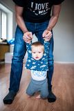 Father holding baby by the hands, helping him to walk. Father holding baby, helping him to walk, the boy is trying to sit on the floor. The room is empty and Royalty Free Stock Photo