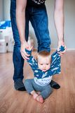 Father holding baby by the hands, helping him to walk Royalty Free Stock Photos