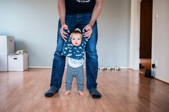 Father holding baby by the hands, helping him to walk. Father holding baby, helping him to walk, the boy is walking barefoot and seems very brave. The room is Stock Photos