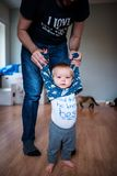 Father holding baby, helping him to walk. The boy is walking barefoot and seems very brave Royalty Free Stock Photography