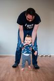 Father holding baby, helping him to walk. The boy is walking barefoot and seems very brave and curious Stock Photo