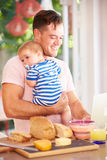 Father Holding Baby And Making Snack Whilst Using Laptop Stock Image