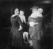 Father holding baby and mother holding a doll Stock Photography