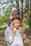 Father holding baby on shoulders Royalty Free Stock Images