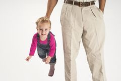 Father holding baby suspended by suspenders Royalty Free Stock Image