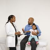 Father holding baby talking to pediatrician. African-American father holding baby girl talking to female pediatrician Stock Photo