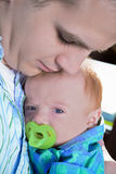 Father holding baby. A father tenderly holds his baby while kissing him on the forehead Royalty Free Stock Photo