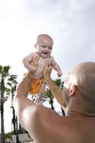 Father holding baby up high in sky. On tropical vacation Royalty Free Stock Images