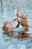 Father holding baby up high in swimming pool. Father holding 6 month old baby up high in swimming pool stock images