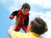 Father holding baby up to sky Royalty Free Stock Photos