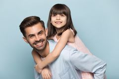 Father holding on back adorable preschool kid studio shot. Handsome father give piggyback daughter, holding on back adorable preschool kid pose look at camera royalty free stock photography