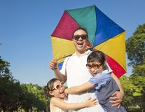 Father holding a colorful umbrella and hug two daughter Royalty Free Stock Photography