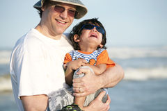 Father holding crying child at beach Stock Images