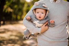 Father holding a cute baby son under arm. Father walking in the park and holding a cute baby son dressed in a romper under arm stock photography