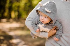 Father holding a cute little son under the arm. Father walking in the park and holding a cute little son dressed in a romper under the arm Stock Photos