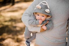 Father holding a cute little son under his arm. Father walking in the park and holding a cute little son dressed in a romper under his arm Stock Image