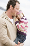 Father holding daughter at beach. Looking away from camera Royalty Free Stock Photography