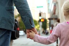 Father holding  the daughter/ child  hand  behind  the traffic lights Stock Images