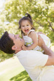 Father holding daughter outdoors Stock Photos