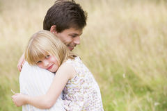 Father holding daughter outdoors smiling Stock Image