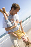Father holding daughter upside down on beach Royalty Free Stock Image