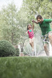 Father holding daughters hand while she jumps through the sprinkler in the garden Stock Images