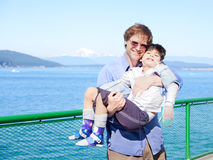 Father holding disabled son in arms on deck of ferry boat. Puget Sound in background. Child has cerebral palsy Royalty Free Stock Photography