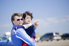 Father holding disabled son on the beach Stock Photos