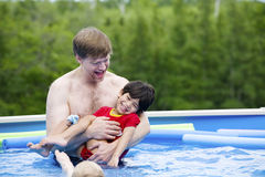 Father holding disabled son in pool Royalty Free Stock Photography