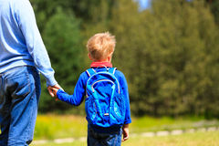 Father holding hand of little son with backpack. Outdoors, back to school stock photography