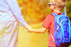 Father holding hand of little son with backpack. Outdoors, back to school Stock Photos