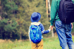Father holding hand of little son with backpack. Outdoors, back to school or daycare Royalty Free Stock Image