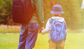 Father holding hand of little son with backpack outdoors. Back to school or daycare royalty free stock images