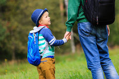 Father holding hand of little son with backpack outdoors. Going to school stock photos